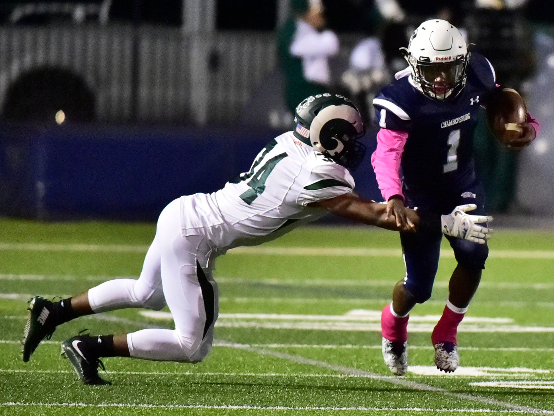 Chambersburg's Kevin Lee (1) returns a kickoff as Timmy Smith (34) of CD makes a tackle. Chambersburg lost to Central Dauphin 35-14 in PIAA football on Friday, Oct. 19, 2018.