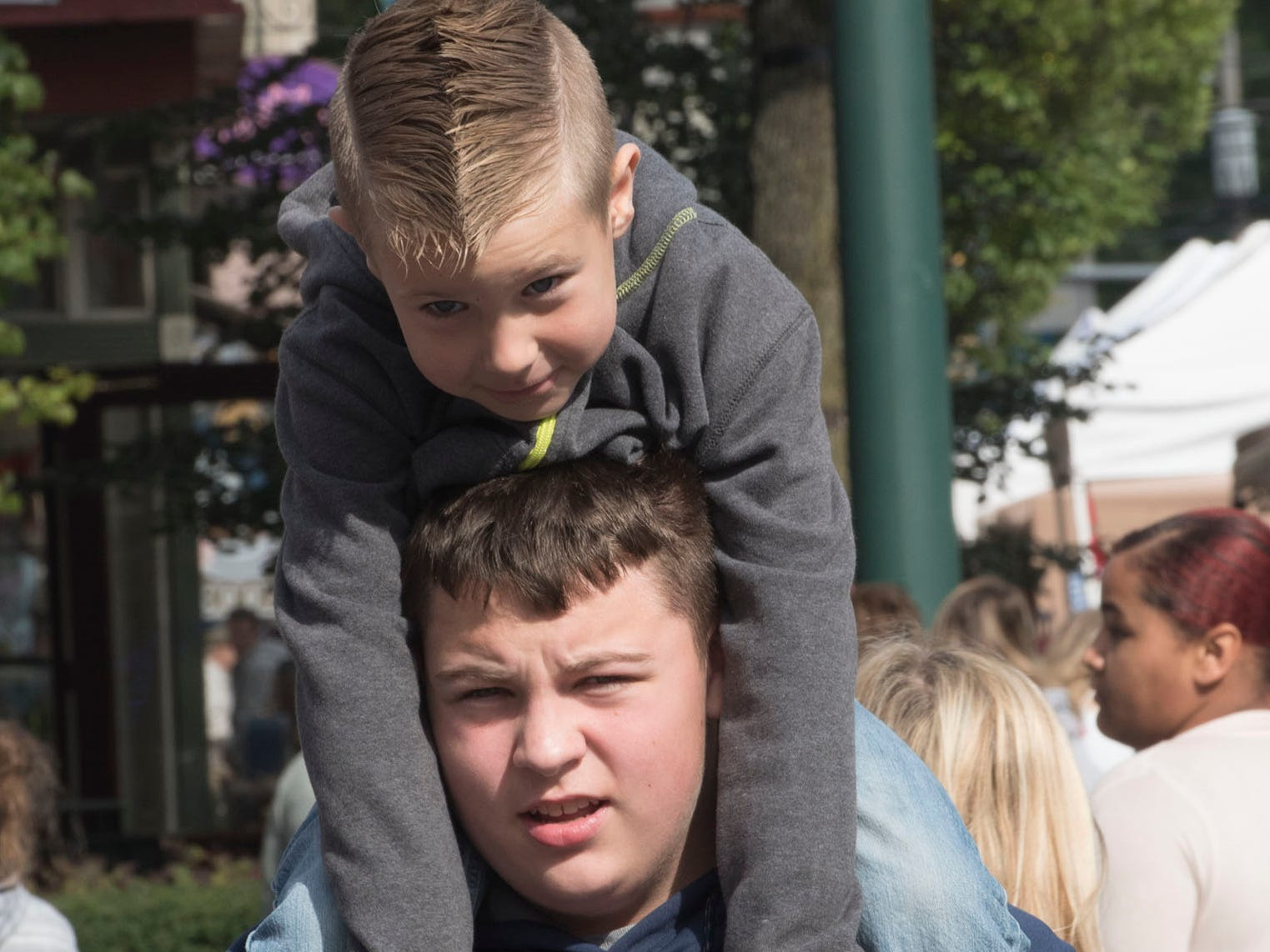 Hayden Ott, 13, gives his cousin Triptyn Barmont, 6, a lift. Applefest started Saturday morning October 20, 2018 in downtown Chambersburg.