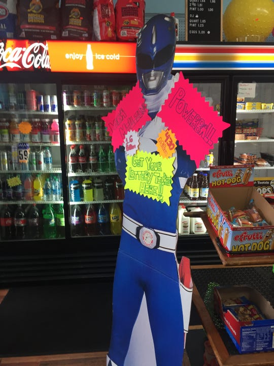 A cardboard Power Ranger displaying the Mega Millions and Powerball jackpots greets customers at West End Bob's News as they come in the store. (Photo by Rebecca Klar)