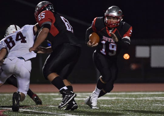 Dover's Justin Johnson goes around a block for a gain Friday night against Gettysburg.