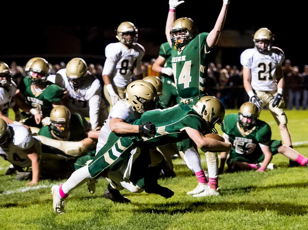 Michael Page signals touchdown as a York Catholic teammate goes into the end zone Friday night.