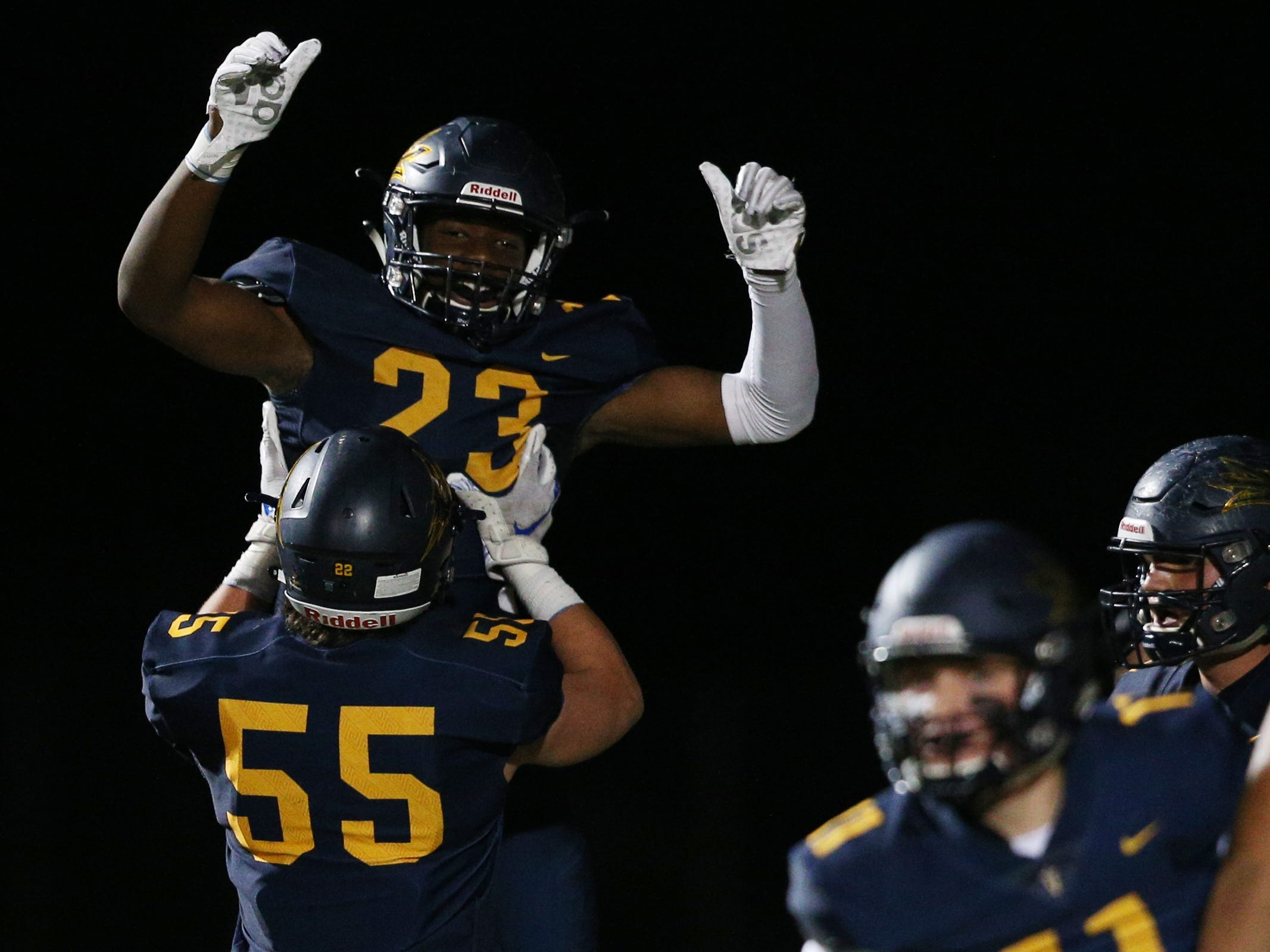 Victor's Rushawn Baker gets a lift from teammate Cal Lambert (55) after one of his two touchdowns on Friday night.