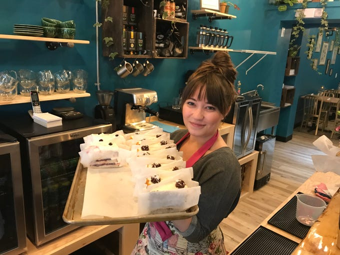 Haley Shuman carries a tray of cake slices at Caramel Bakery and Bar.