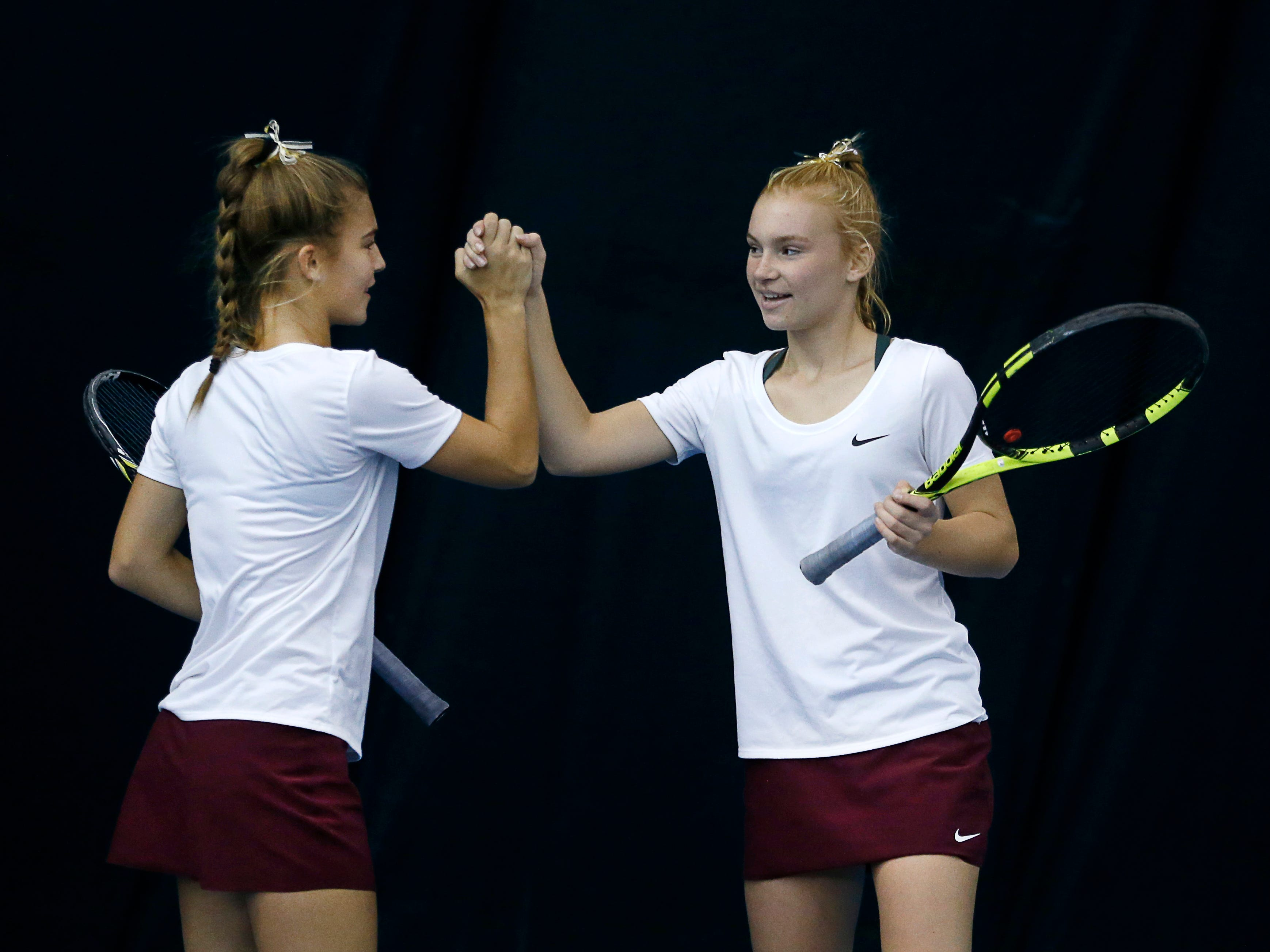 Pittsford Mendon's Sarah Bodewes high fives her sister Jess during the doubles final of the Section V Tennis State Qualifiers at Mendon Racquet & Pool Club. Sarah and Jess won 6-1, 6-1.