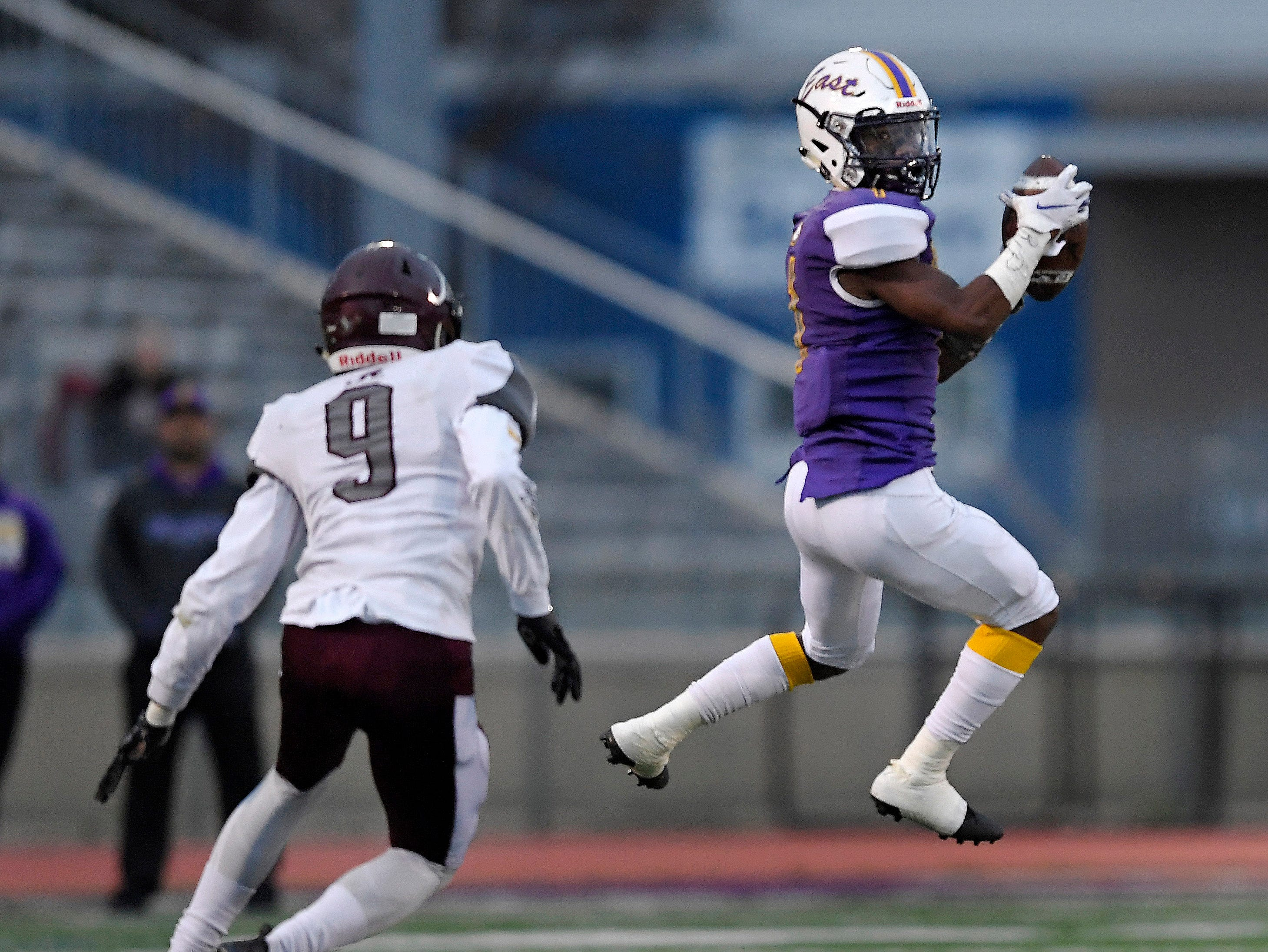 East's Seven McGee, right, catches a pass in front of Greece Arcadia's Shakim Harris during a Class A sectional quarterfinal played at East High School, Friday, Oct. 19, 2018.
