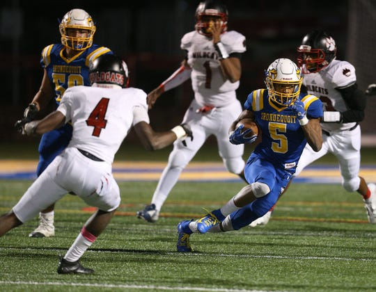 Irondequoit's Jadon Turner cuts back against Wilson's Jah'Kier Moore.