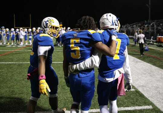From left, Irondequoit's Kyle Taylor, Jadon Turner and Joshua Colon walk off the field after beating Wilson 35-27.