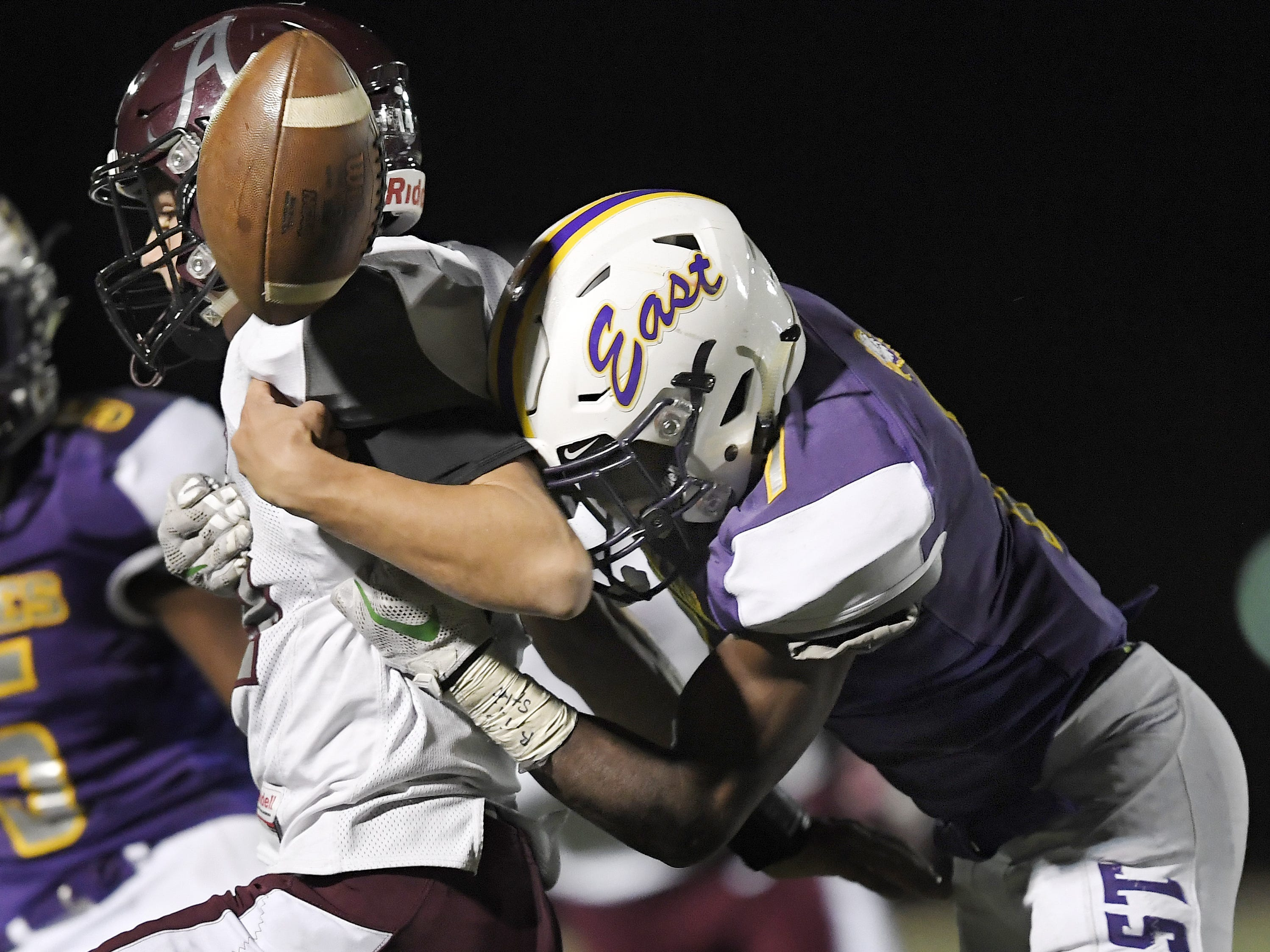 East's Seven McGee, right, forces a fumble by Greece Arcadia's Brian Shonitsky during a Section V Class A quarterfinal at East.