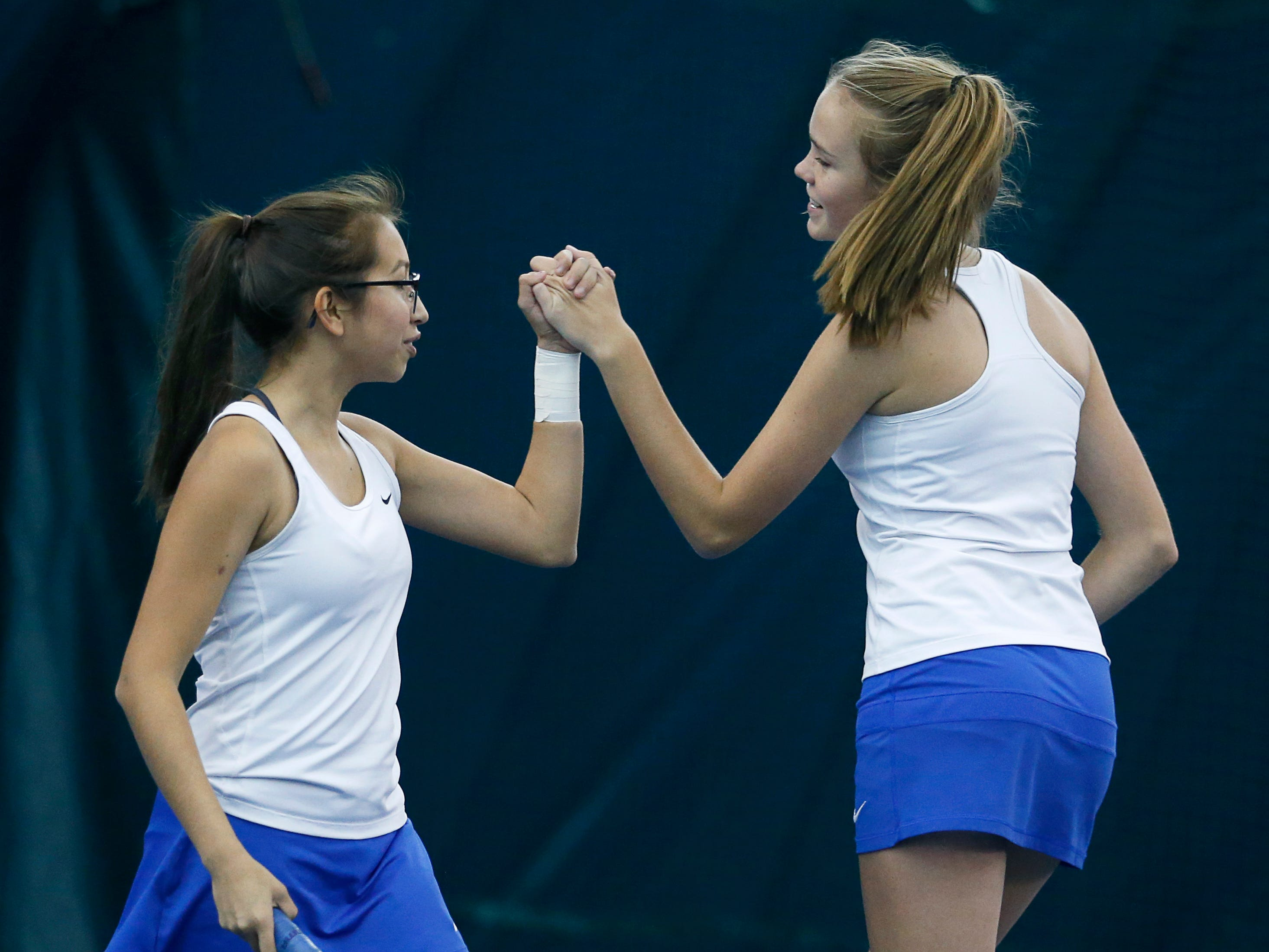 Webster's Stephanie Romero and Alexa Monrad high-five while playing for third place in the doubles of the Section V Tennis State Qualifiers at Mendon Racquet & Pool Club.