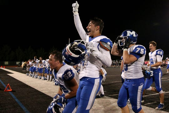 McNary teammates celebrate after his defeating West Salem, 35-23, at West Salem High School on Friday, Oct. 19.