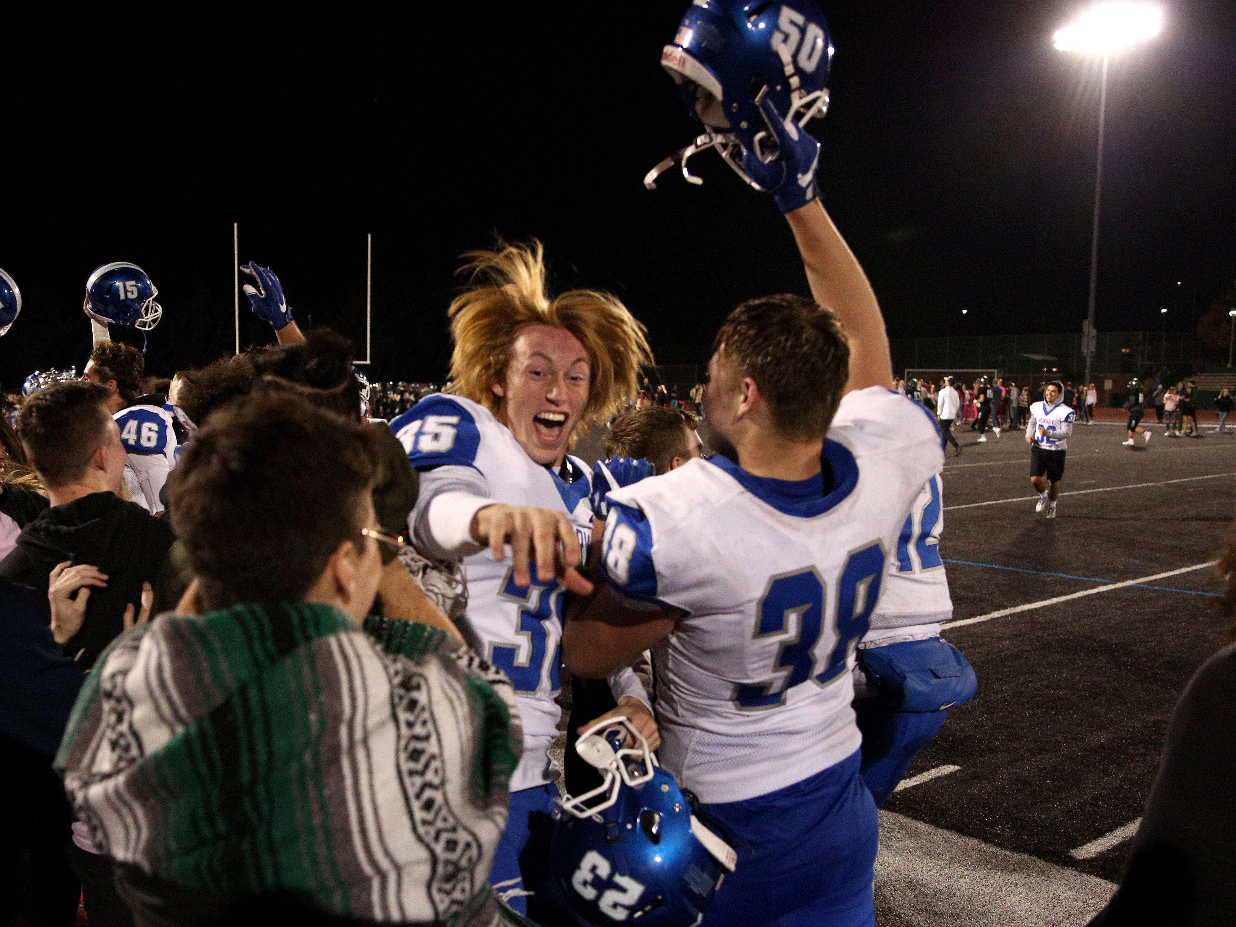 McNary teammates celebrate after his defeatingWest Salem, 35-23, at West Salem High School on Friday, Oct. 19.