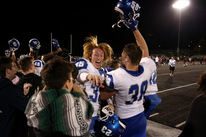 McNary teammates celebrate after defeating West Salem, 35-23, at West Salem High School on Friday.