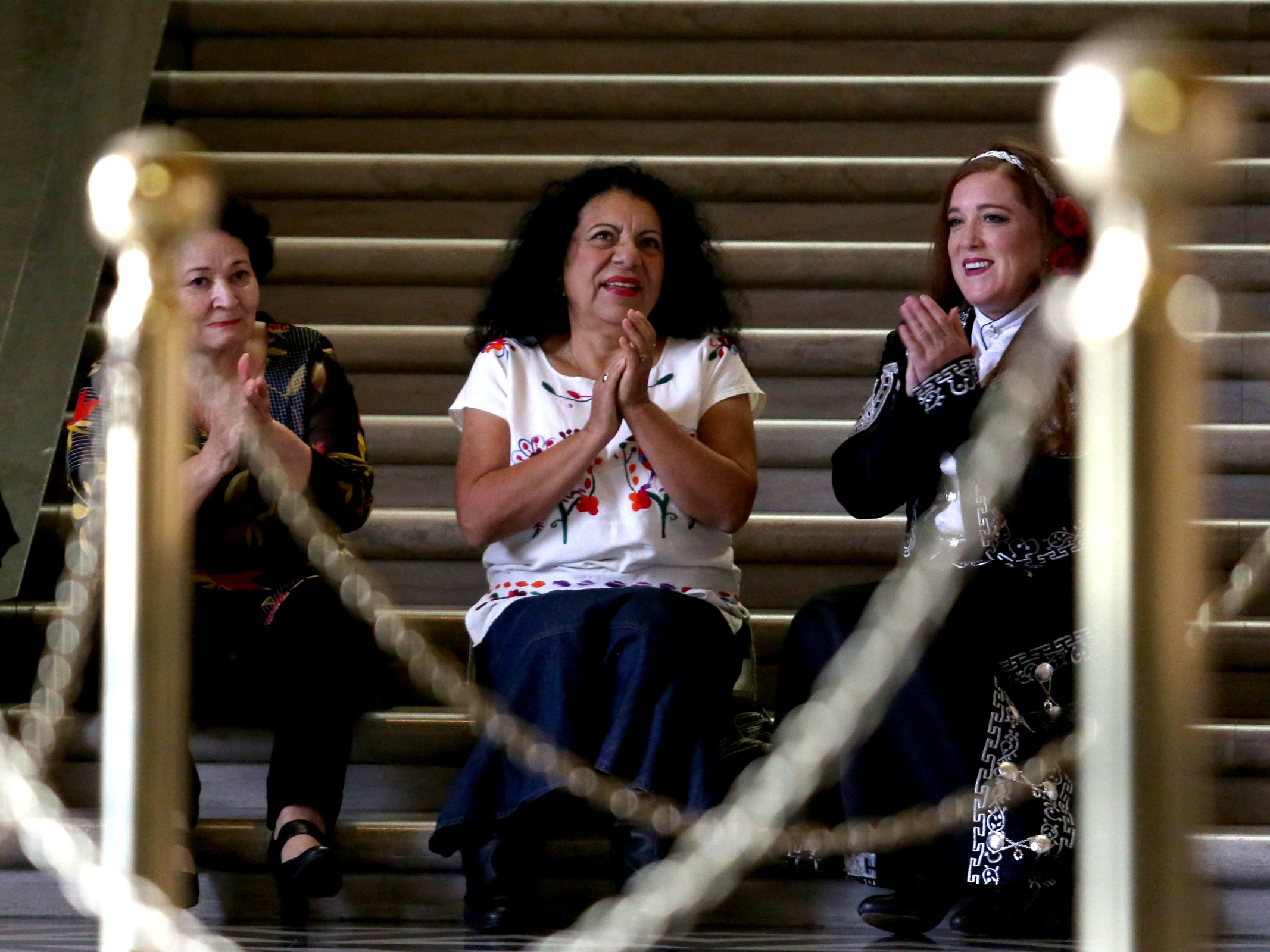 Angela Miranda, from left, of Salem, Mago Gilson, of Eugene, and Susana Arroyo, of Albany, applaud a guitar player during Hispanic Heritage Day at the Oregon State Capitol on Saturday, Oct. 20, 2018.