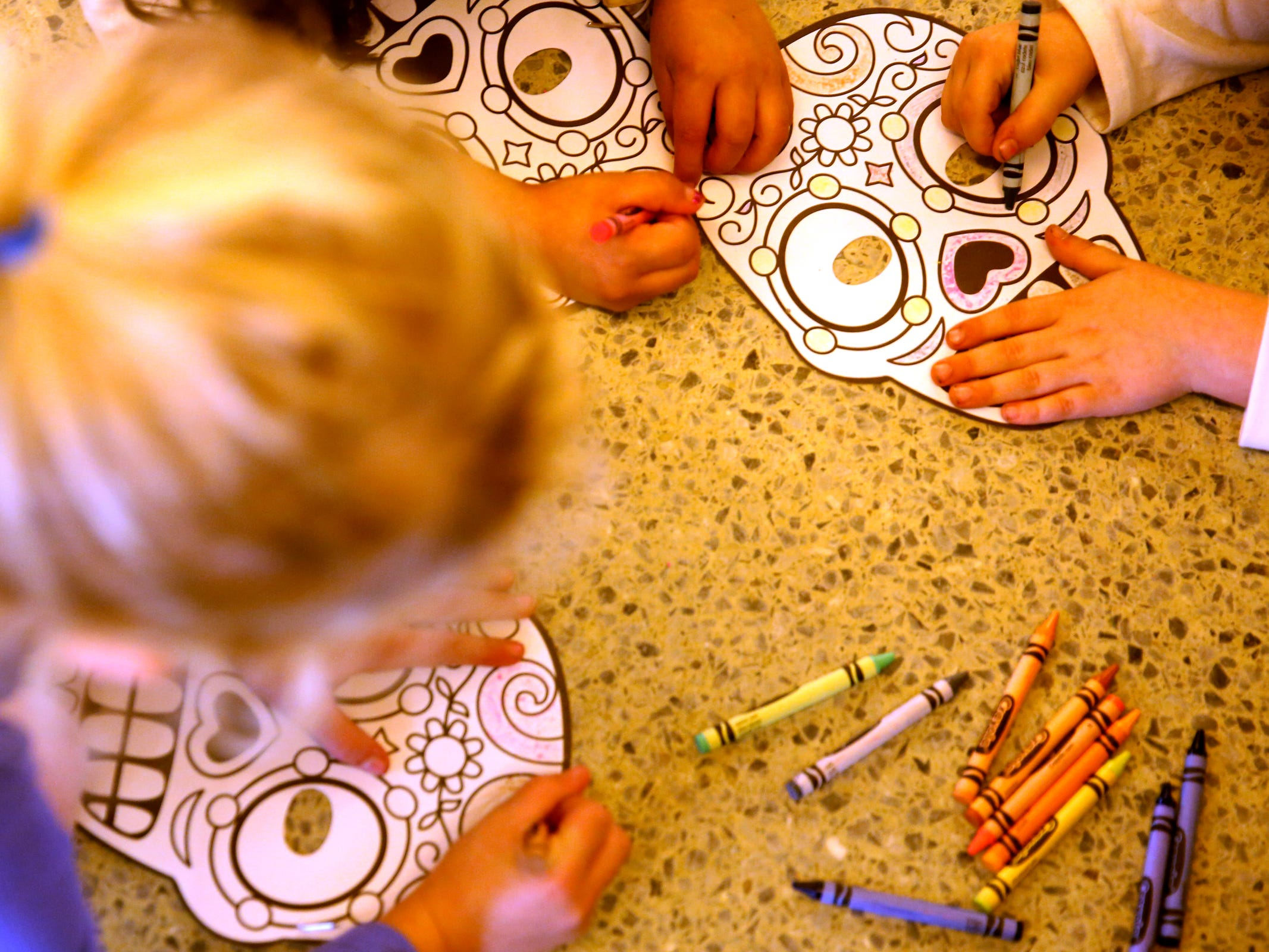 Children color decorated skulls, part of the Dia de los Muertos holiday, during Hispanic Heritage Day at the Oregon State Capitol on Saturday, Oct. 20, 2018.
