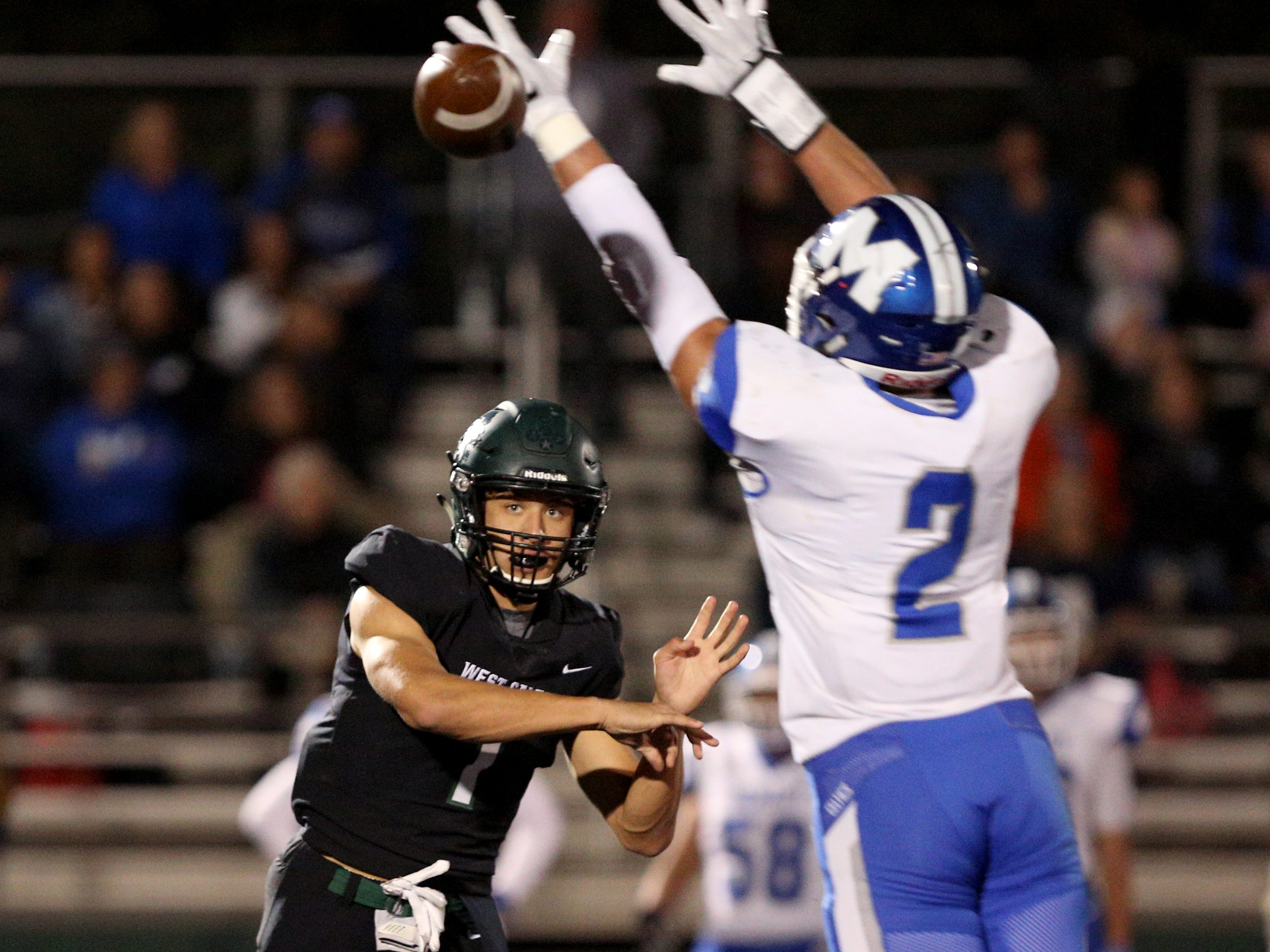 West Salem's Simon Thompson (1) makes a pass across McNary defender Jr. Walling (2) during the first half of the McNary vs. West Salem football game at West Salem High School on Friday, Oct. 19.