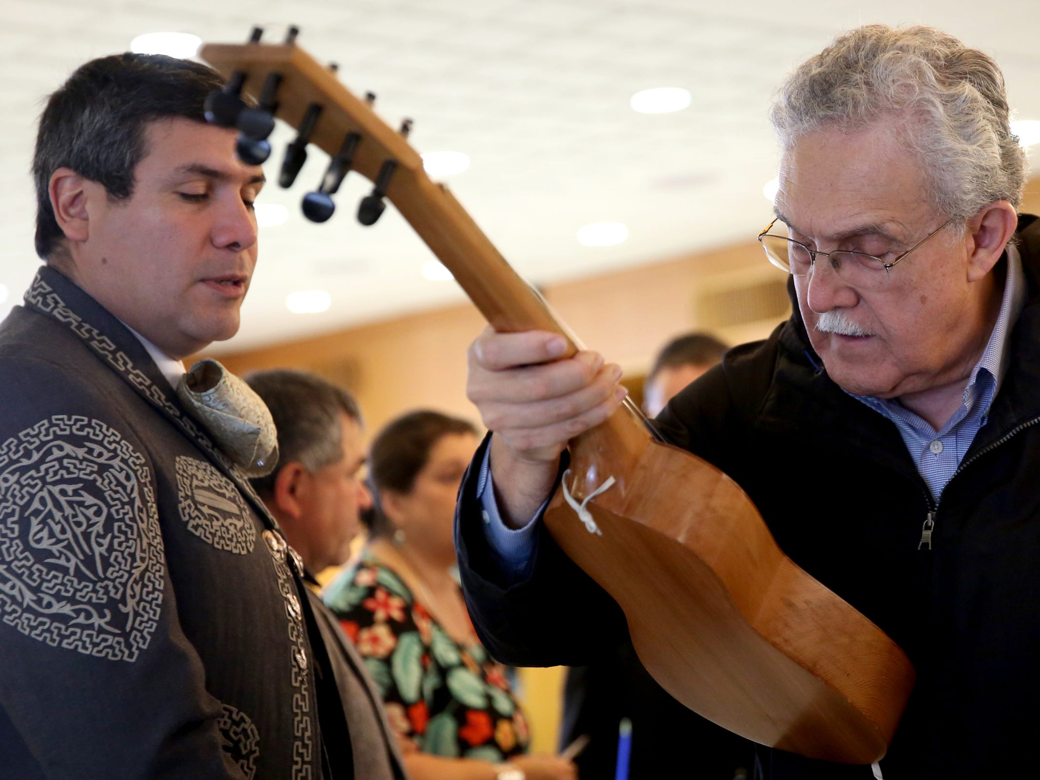 F. Javier Navarro, left, and Efrain Diaz-Horna, both of Salem, look over a jarana, a guitar-like instrument from Mexico, during Hispanic Heritage Day at the Oregon State Capitol on Saturday, Oct. 20, 2018.