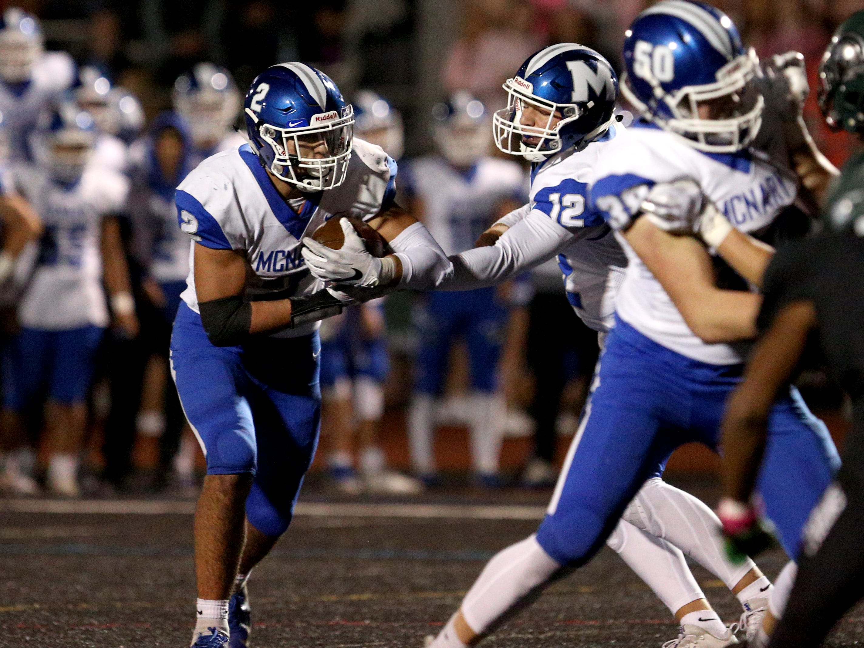 McNary's Erik Barker (12) hands the ball off to Jr. Walling (2) during the first half of the McNary vs. West Salem football game at West Salem High School on Friday, Oct. 19.
