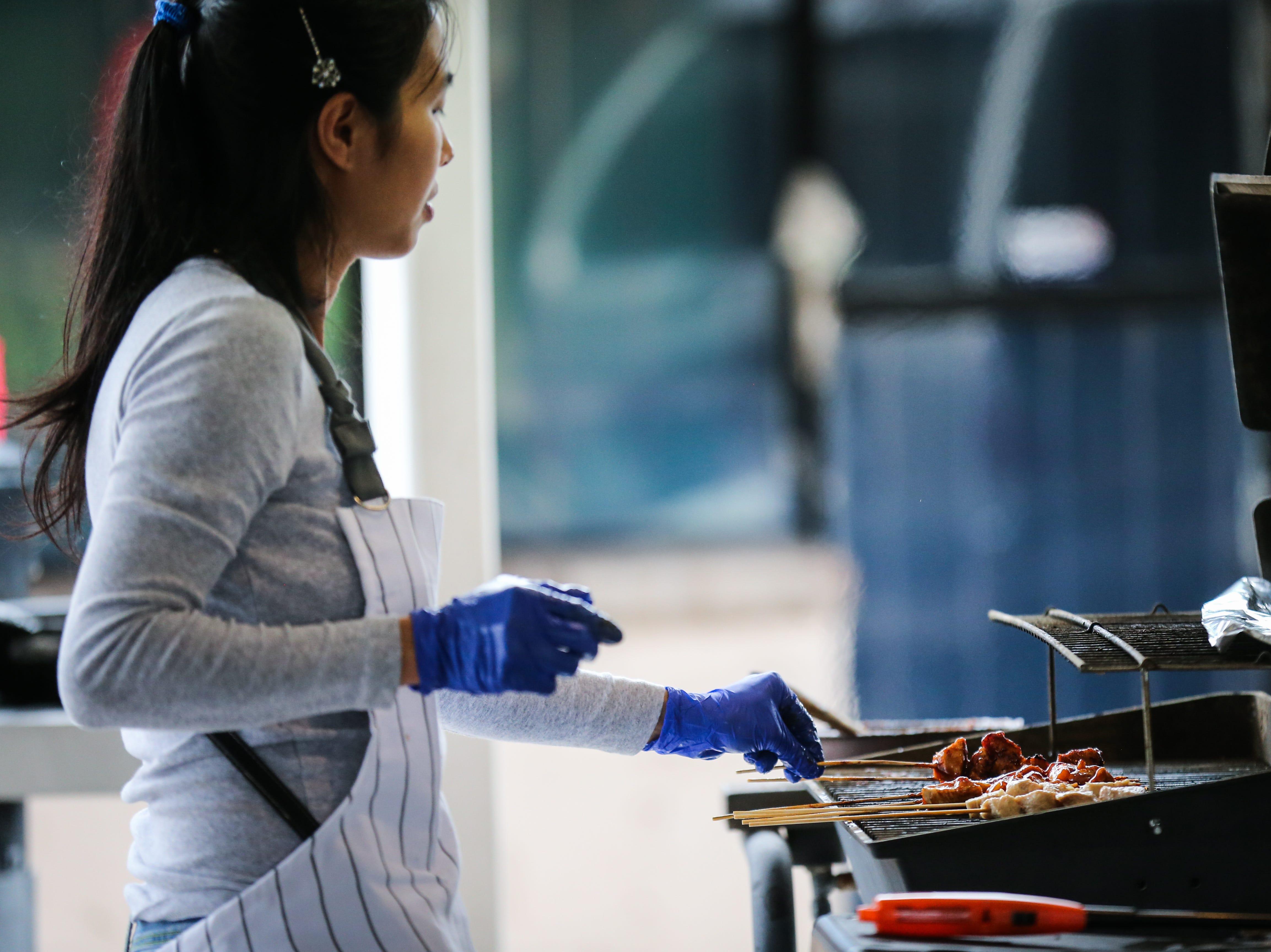 A vendor grills up meat during the Asian Bazaar Saturday, Oct. 20, 2018, at El Paseo de Santa Angela.