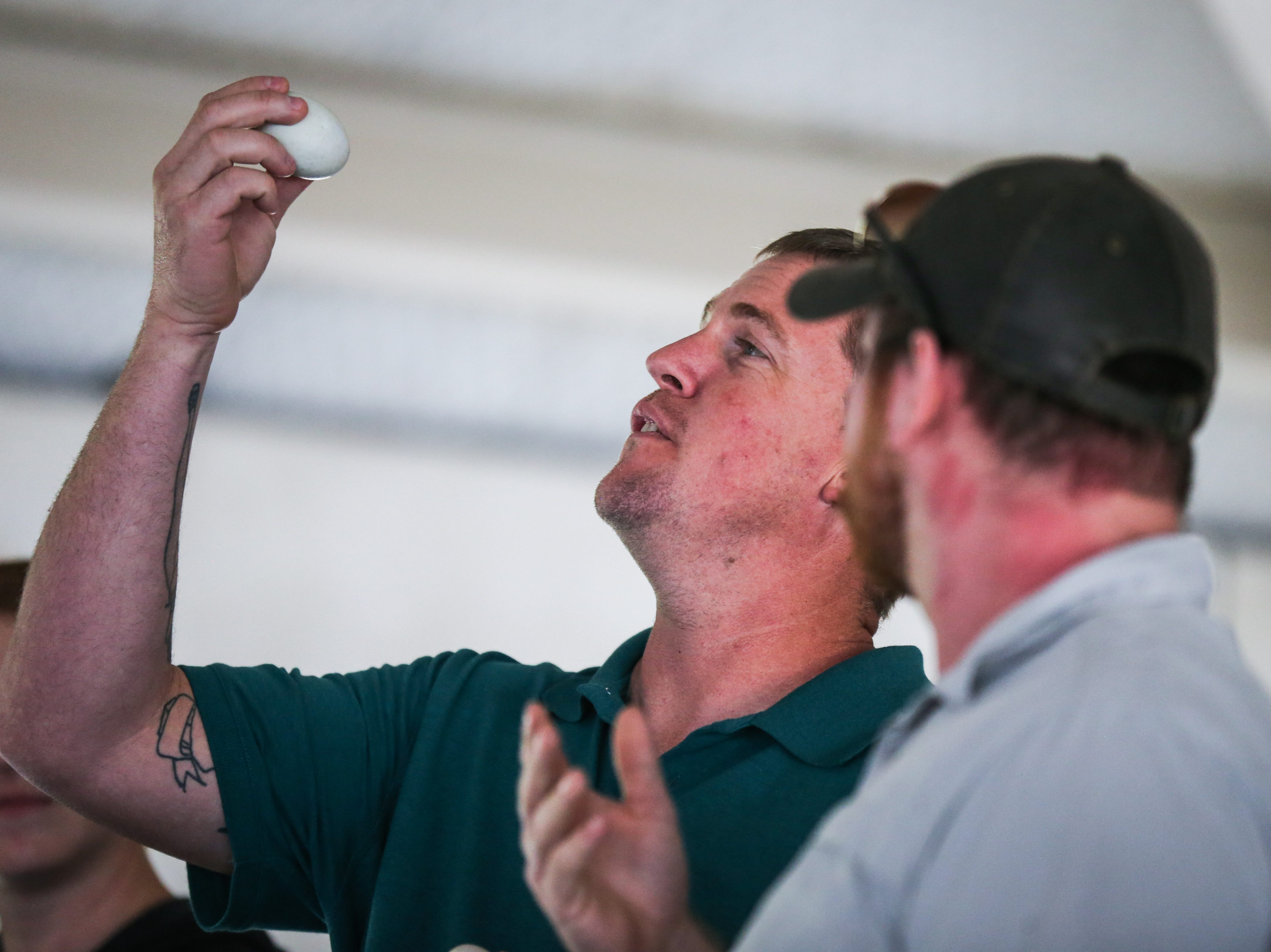 Wes Richardson and Harry Briggs look at the balut they are about to eat in a contest during the Asian Bazaar Saturday, Oct. 20, 2018, at El Paseo de Santa Angela.
