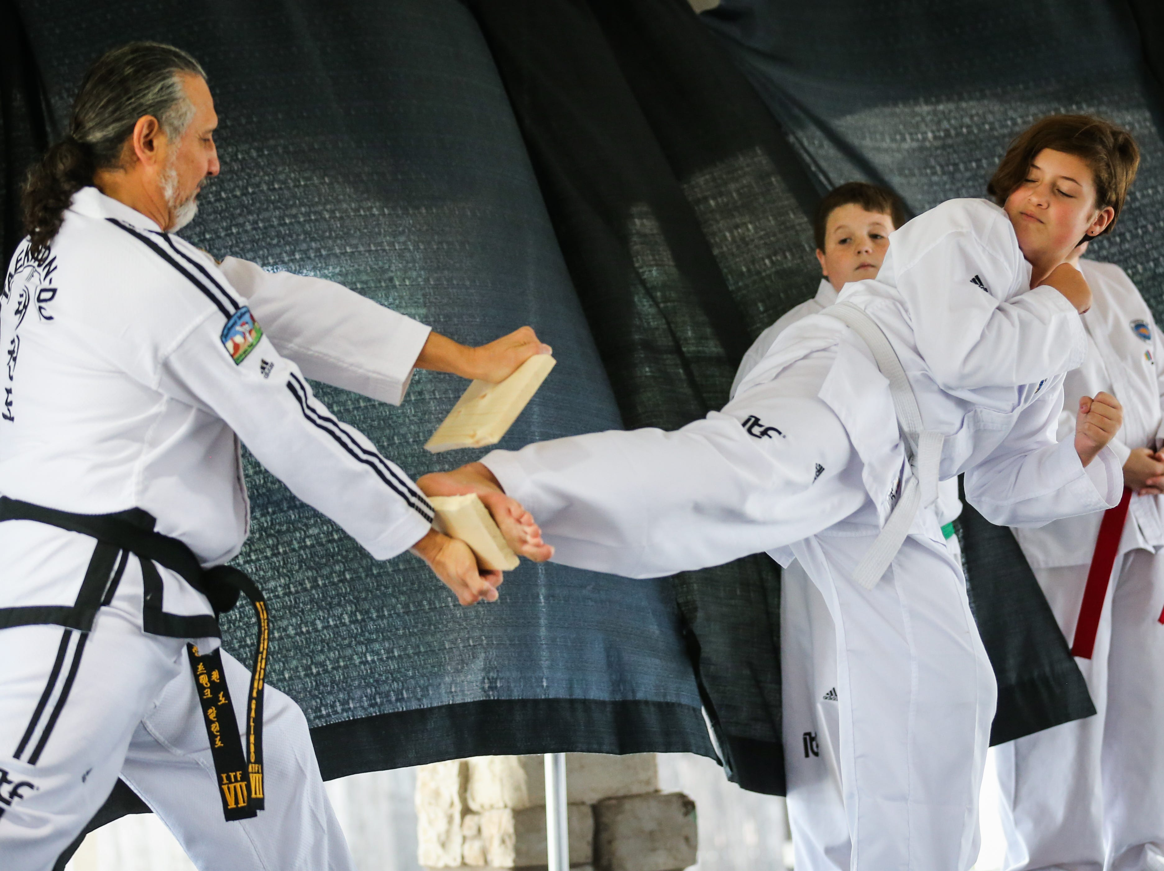 Frank Gailndo with Southwest TaeKwon-Do holds a board for Lanaya Underhill, 12, to break during a demonstration at the Asian Bazaar Saturday, Oct. 20, 2018, at El Paseo de Santa Angela.