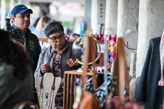 Attendees look over jewelry and accessories during the Asian Bazaar Saturday, Oct. 20, 2018, at El Paseo de Santa Angela.