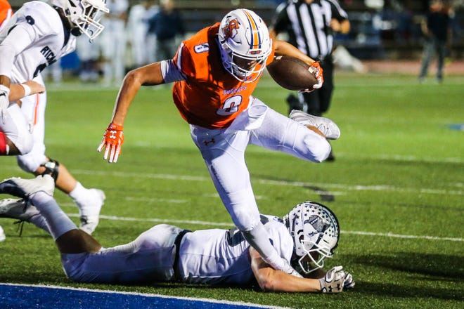 Central's Malachi Brown jumps over a Fort Worth Richland defender to score a touchdown Friday, Oct. 19, 2018, at San Angelo Stadium.