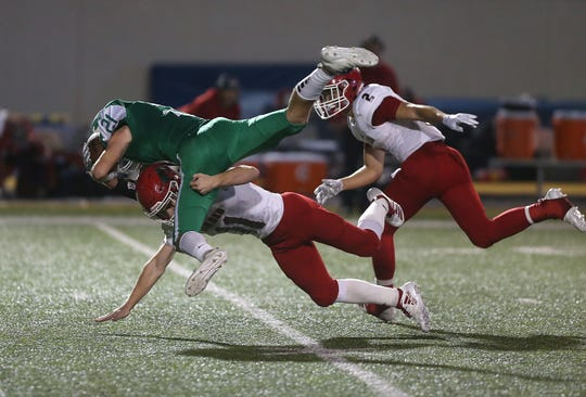 Wall's Lane Ashley (#21) is tackled midair after catching a pass during the game Friday, Oct. 19, 2018 by Jim Ned's Joshua Kelso (#11) at LeGrand Stadium.