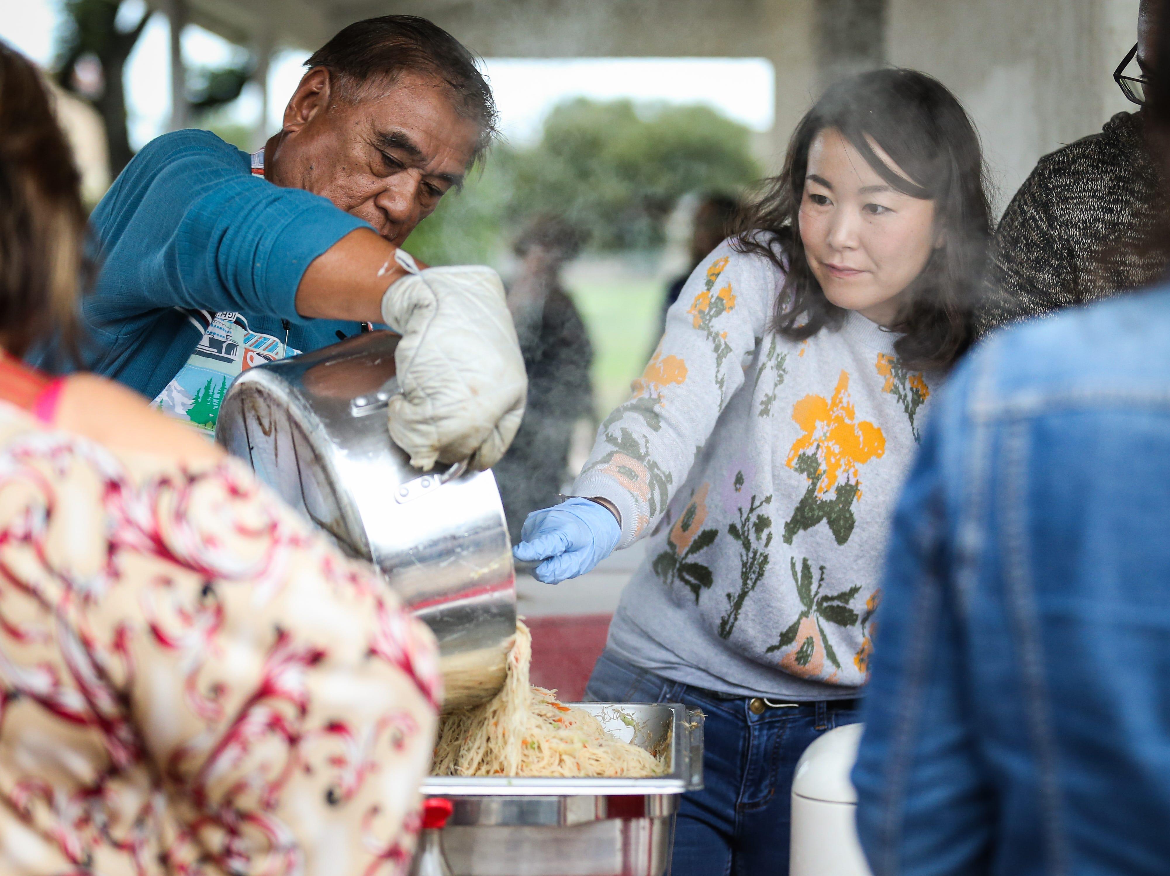 Vendors pour out noodles to a serving tray during the Asian Bazaar Saturday, Oct. 20, 2018, at El Paseo de Santa Angela.