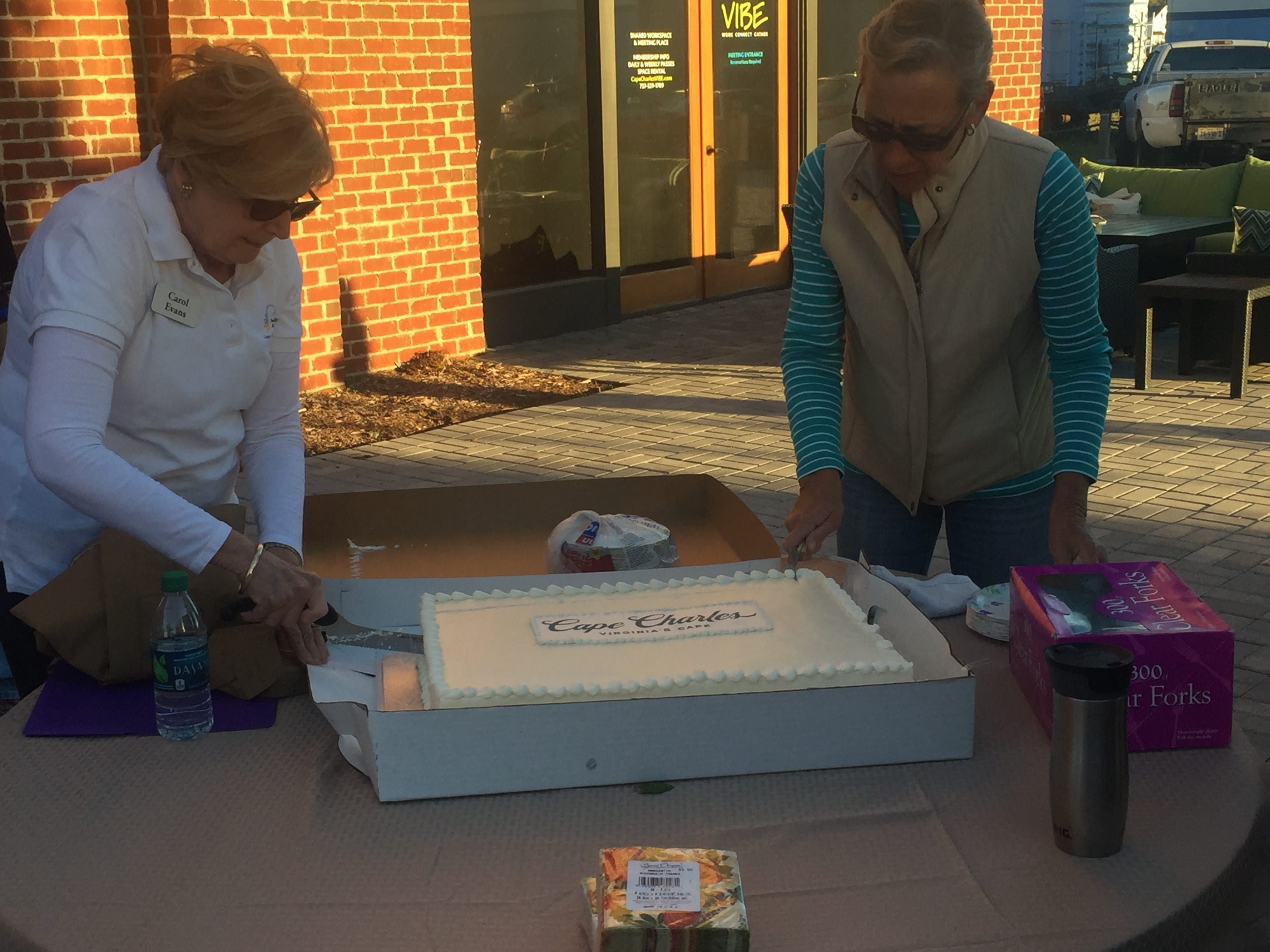 Cape Charles volunteers cut a cake during a ceremony celebrating the town's new brand and logo on Friday, Oct. 19, 2018 in Cape Charles, Virginia.