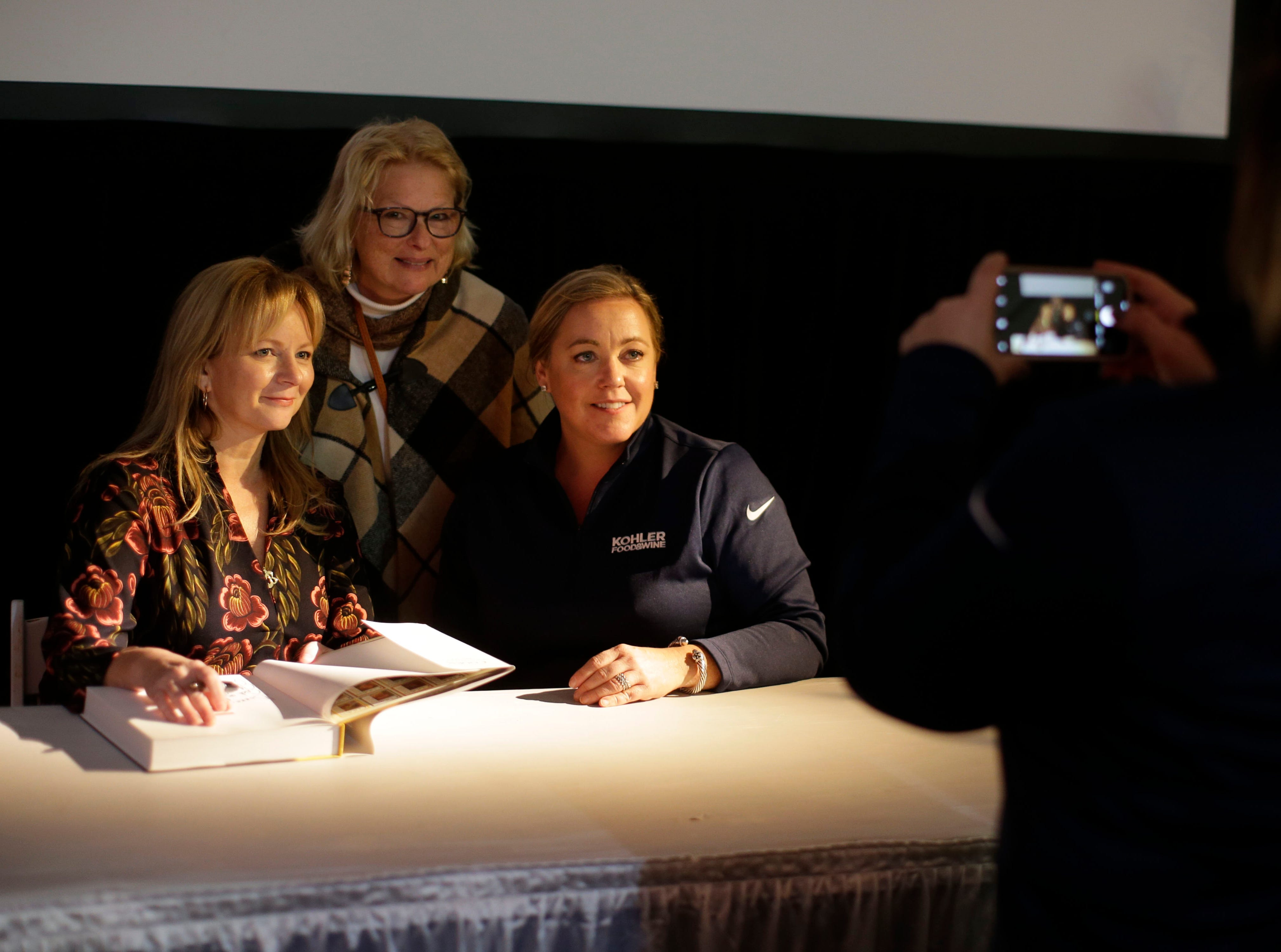 America's Test Kitchen's Bridget Lancaster, left seated, and Julia Collin Davison, right seated, poses with a guest at Kohler Food and Wine, Saturday, October 20, 2018, in Kohler, Wis.