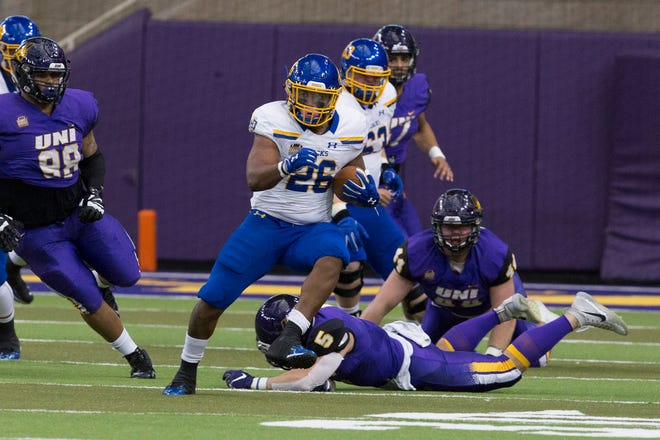South Dakota State's Mikey Daniel carries the ball as he jumps over UNI's Martavin Hall as he tries to make a tackle during Saturday evening's game.