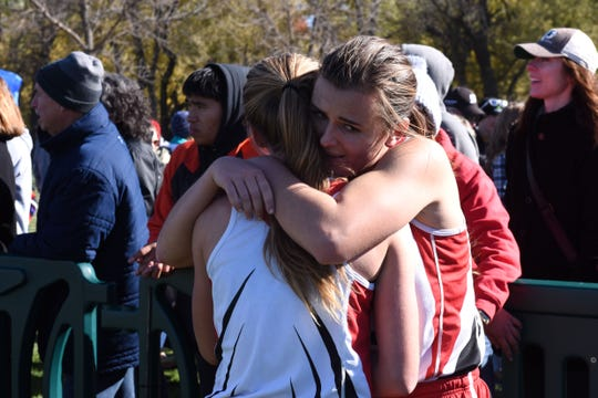 Ella Byers (315) is embraced after winning the Class A girls state cross country meet at Yankton Trail Park in Sioux Falls, S.D., Saturday, Oct. 20, 2018.