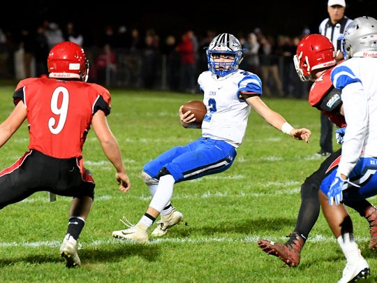 Robert E. Lee quarterback William Dod holds up with the ball as he faces off against Riverheads' Elijah Dunlap and another player during a football game played in Greenville on Friday, Oct. 19, 2018.