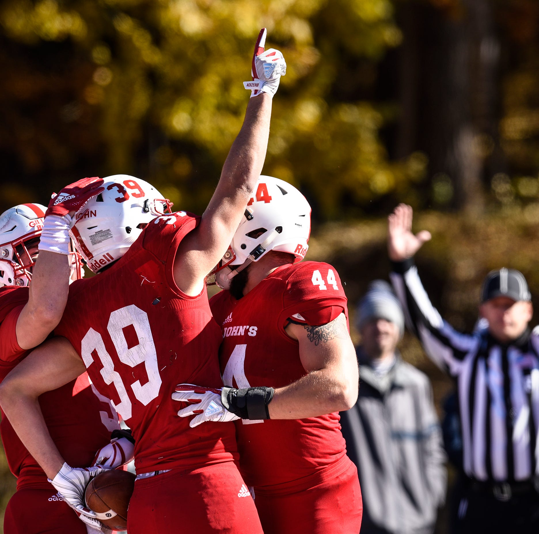 Tommy Auger raises his hand skyward after scoring a touchdown during the first half of the Saturday, Oct. 20, game against St. Olaf at Clemens Stadium in Collegeville