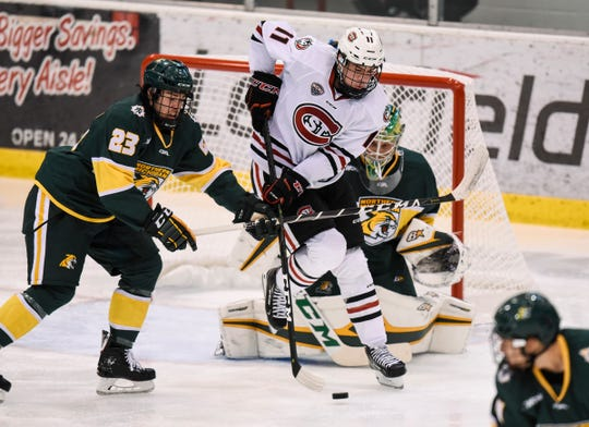 St. Cloud State's Ryan Poehling tries to control the puck during the second period of the Friday, Oct. 19, game in front of  Northern Michigan goaltender Atte Tolvanen at the Herb Brooks National Hockey Center in St. Cloud.