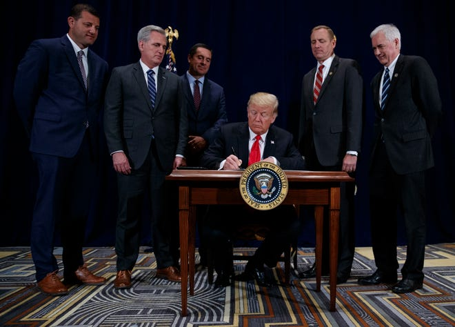 "President Donald Trump signs a ""Presidential Memorandum Promoting the Reliable Supply and Delivery of Water in the West,"" during a ceremony on Oct. 19, 2018, in Scottsdale, Arizona. Standing behind him are (from left) Republican U.S. Reps. David Valadao, Kevin McCarthy, Devin Nunes, Jeff Denham and Tom McClintock of California."