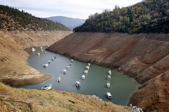 In this Oct. 30, 2014, photo, houseboats float in the drought-lowered waters of Oroville Lake near Oroville, Calif. The lake is the State Water Project's principal reservoir. The order President Donald Trump signed Oct. 19, 2018, aims to help the State Water Project and others.