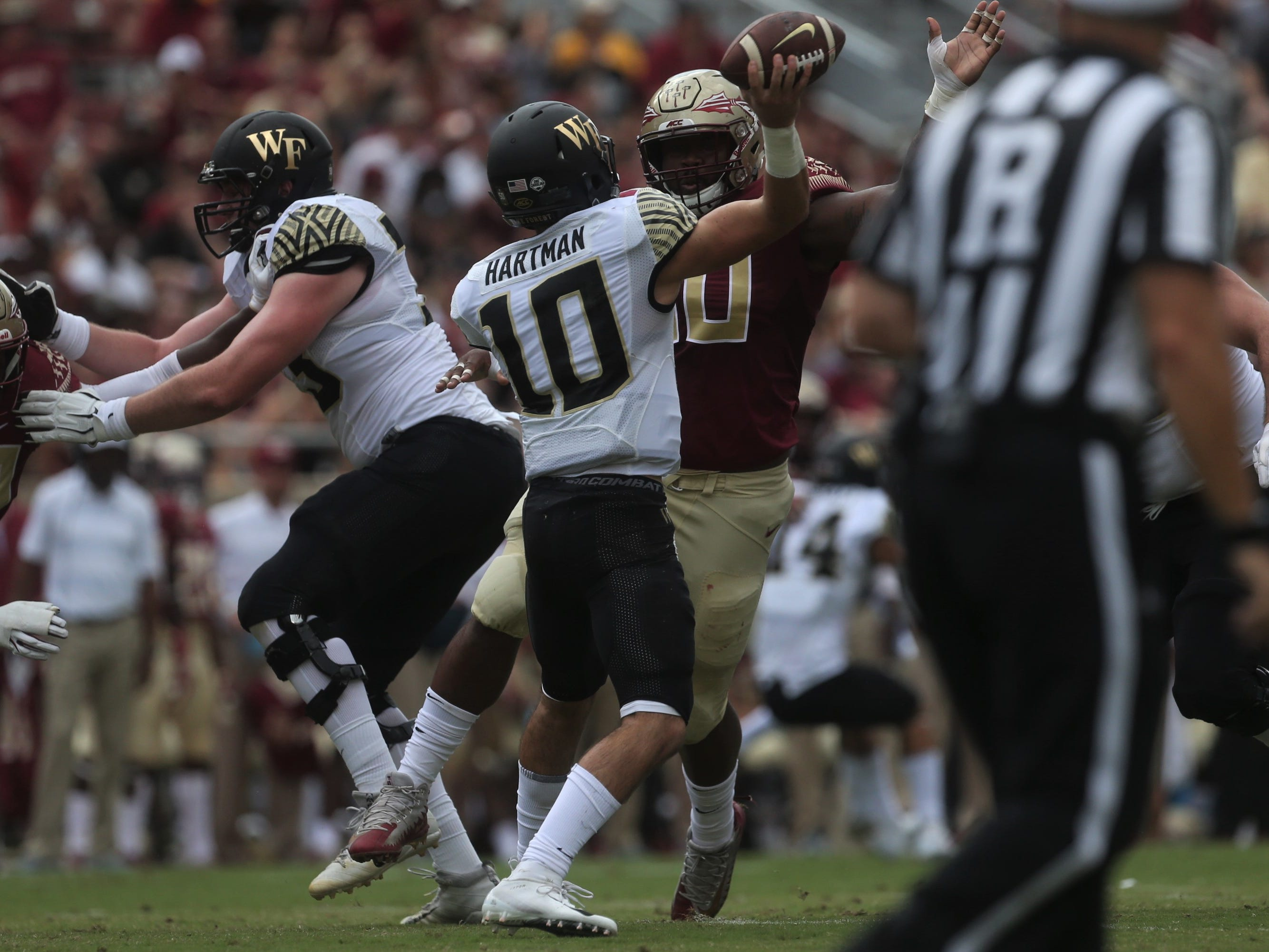 Wake Forest quarterback Sam Hartman tries to get a pass off over the rush of Florida State defensive tackle Demarcus Christmas during a game at Doak Campbell Stadium on Saturday, Oct. 20, 2018.