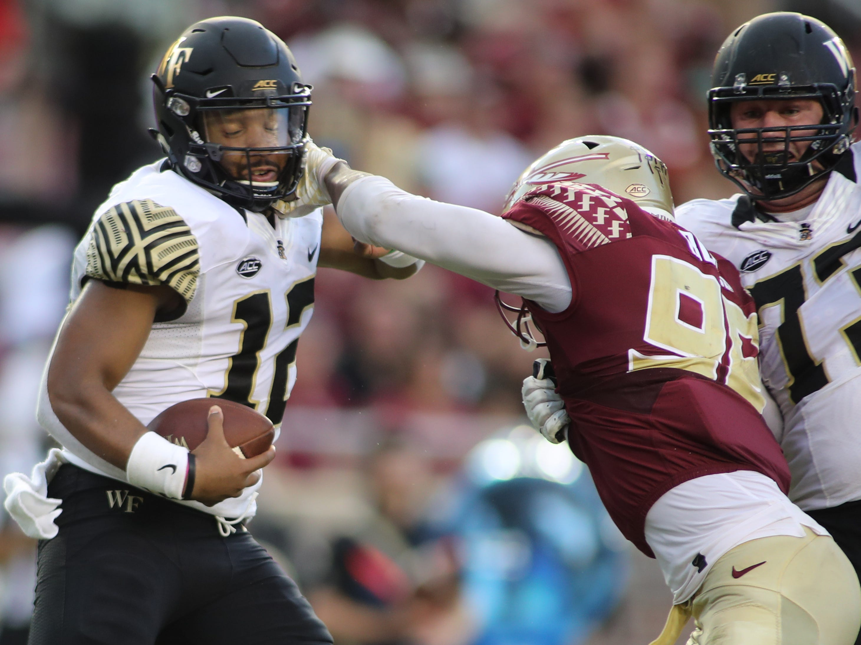 Florida State Seminoles defensive end Brian Burns (99) grabs the face mask of Wake Forest Demon Deacons quarterback Jamie Newman (12) during FSU's homecoming game against Wake Forest at Doak S. Campbell Stadium Saturday, Oct. 20, 2018.