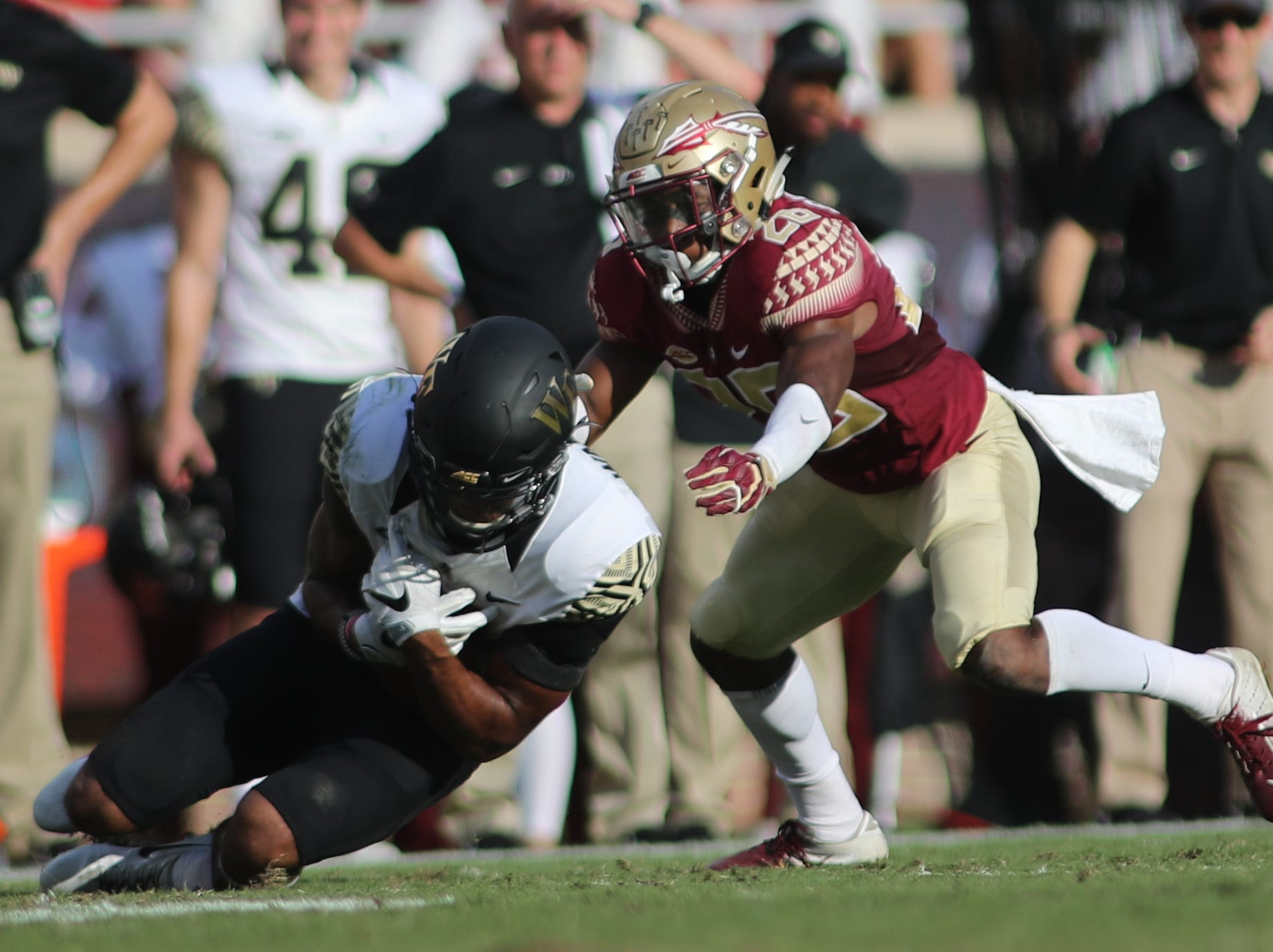 Wake Forest Demon Deacons wide receiver Scotty Washington (7) goes down after a catch followed by Florida State Seminoles defensive back Asante Samuel Jr. (26)  during FSU's homecoming game against Wake Forest at Doak S. Campbell Stadium Saturday, Oct. 20, 2018.