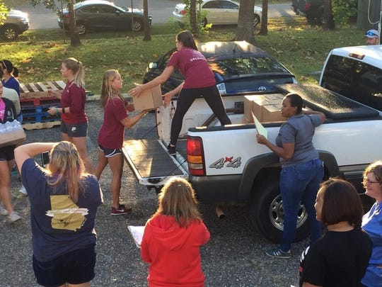 Volunteers load pickup trucks with goods at Second Harvest to deliver to communities in need.
