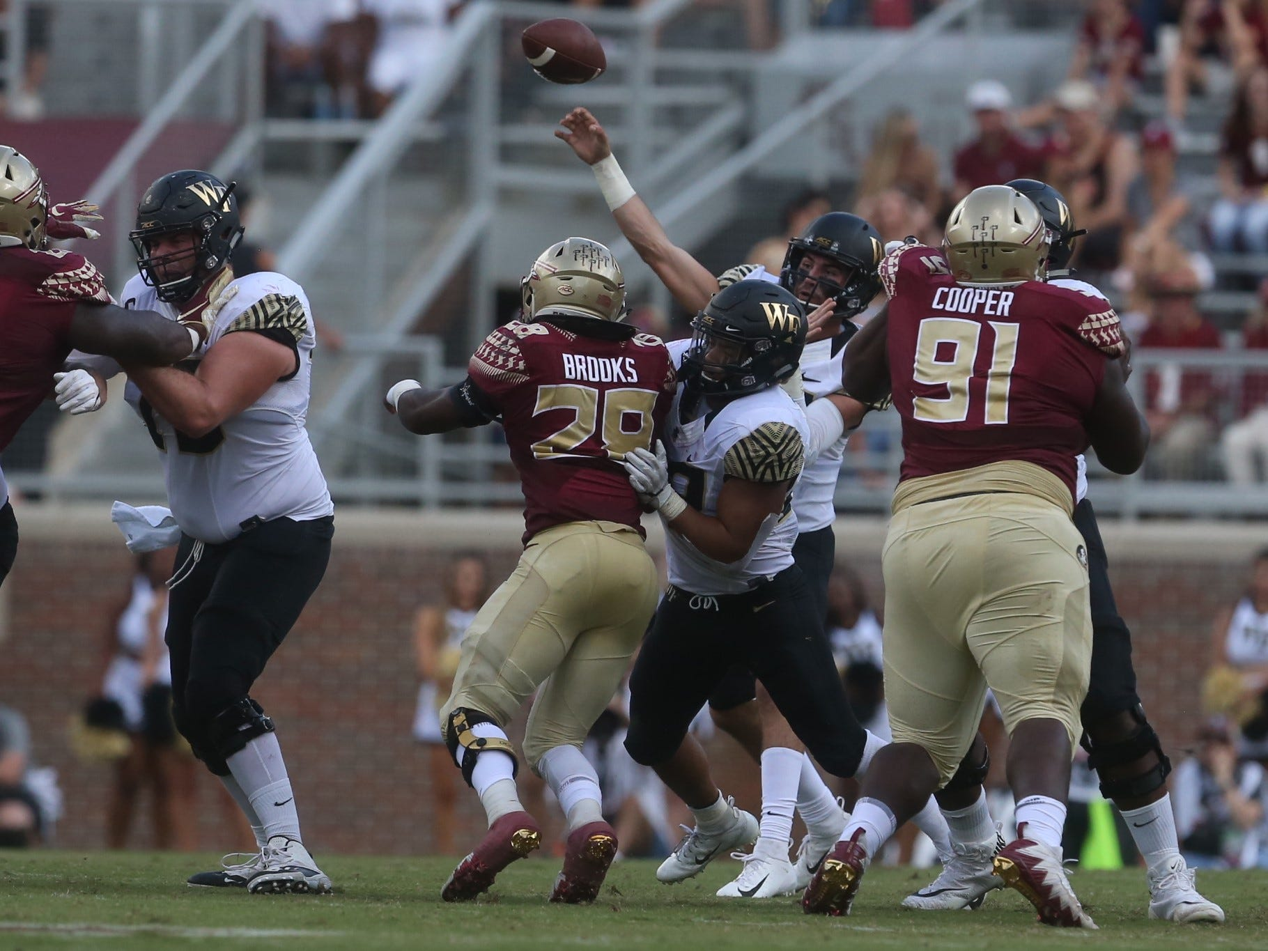 Wake Forest quarterback Sam Hartman throws a pass downfield as Florida State tries to get a pass rush during a game at Doak Campbell Stadium on Saturday, Oct. 20, 2018.