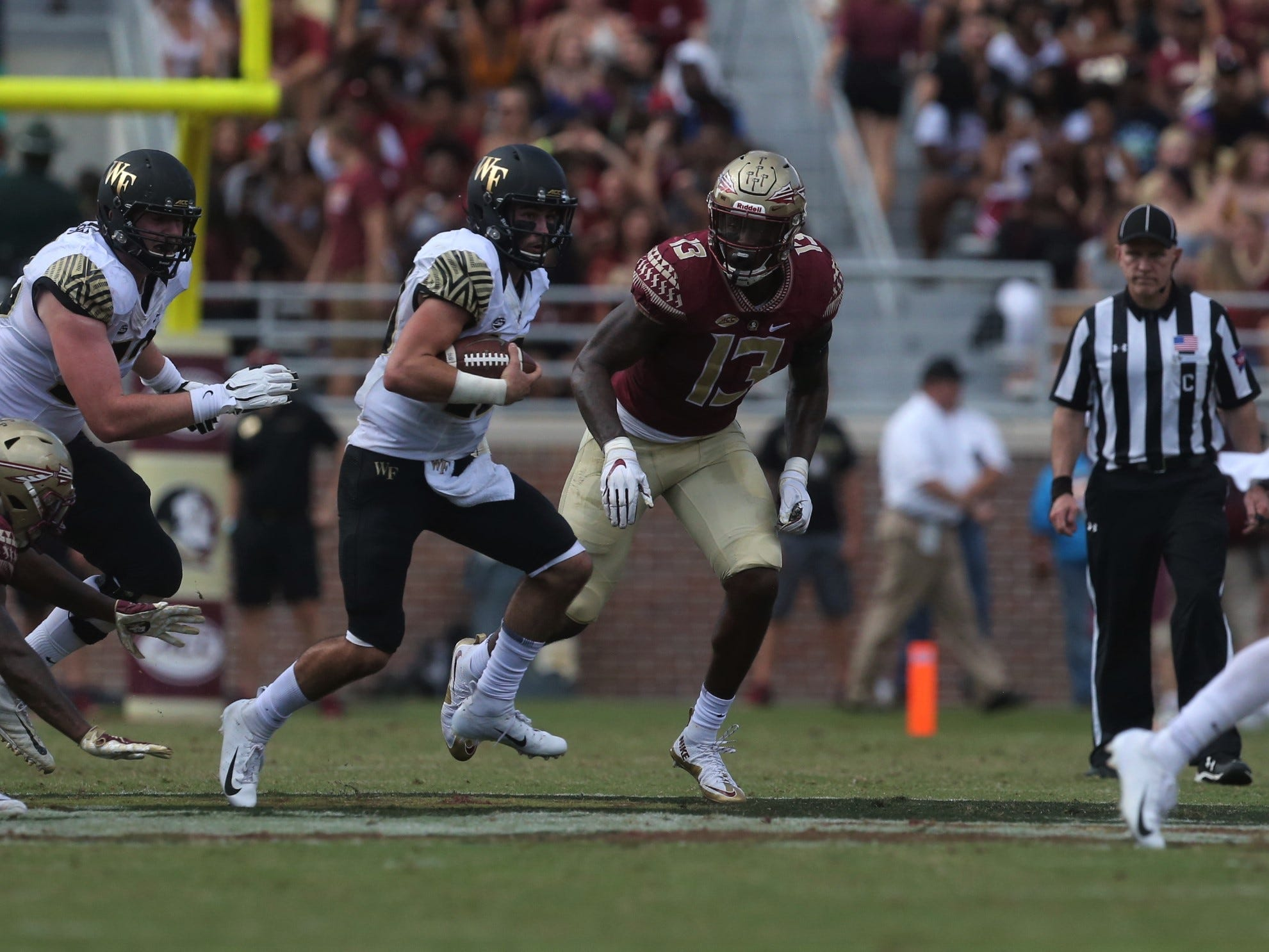 Wake Forest quarterback Sam Hartman rushes for a gain past Florida State defensive end Joshua Kaindoh during a game at Doak Campbell Stadium on Saturday, Oct. 20, 2018.
