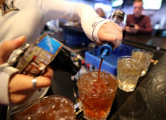 A bartender at Buzz's Pub & Grill pours a few old fashioneds using Gary's Old Fashioned Mix Thursday, Oct. 4, 2018, in Freedom, Wis. Danny Damiani/USA TODAY NETWORK-Wisconsin