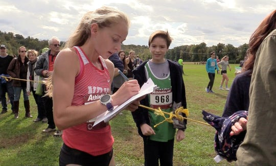 North Rockland's Katelyn Tuohy signs an autograph for a fan after winning the second girls varsity race Saturday during the Section 1 Coaches Cross-Country Invitational at Bowdoin Park in Wappingers Falls.