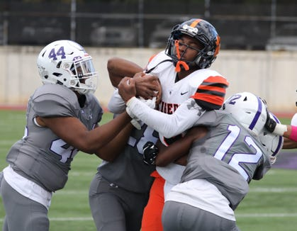 White Plains quarterback Marcus Andre is brought down by New Rochelle's Corey Baron and Jessie Parson during the Class AA quarterfinal playoff game Saturday at New Rochelle High School.