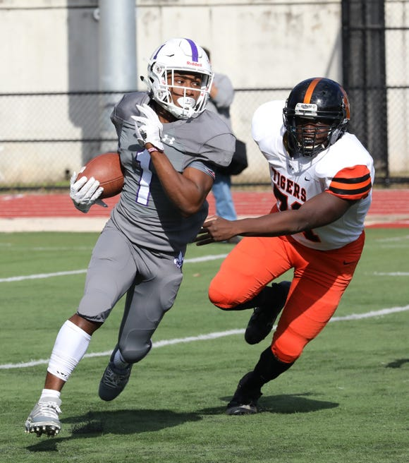 Omari Walker from New Rochelle runs with the ball during the Class AA quarterfinal playoff game Saturday against White Plains at New Rochelle High School.