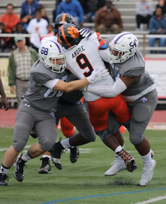 White Plains quarterback Marcus Andre is brought down by New Rochelle's Ethan Marlow and Jaheim Jones during the Class AA quarterfinal playoff game Saturday.