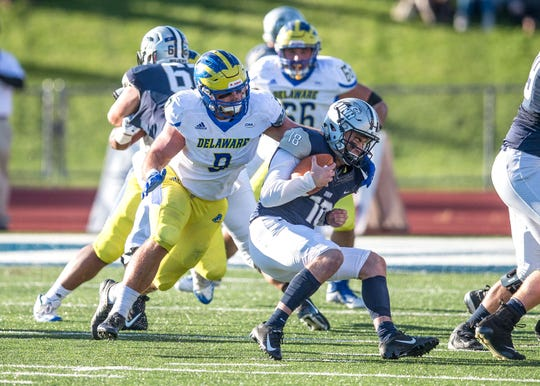 Delaware's Troy Reeder bears down on UNH quarterback Trevor Knight for a sack.