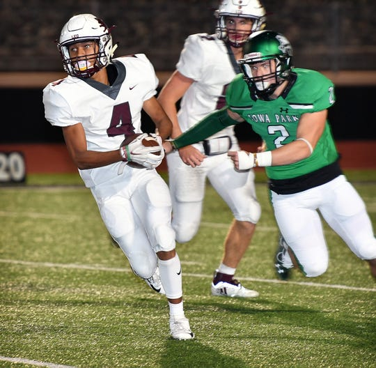 Vernon runningback Ismael Ortega (4) moves the ball as Iowa Park's Creed Wells (2) pursues during their game Friday night in Iowa Park.